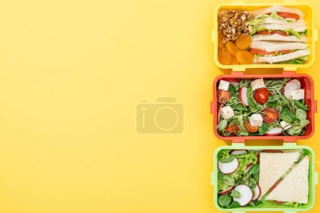 Photo for Top view of three lunch boxes with food  on yellow background - Royalty Free Image