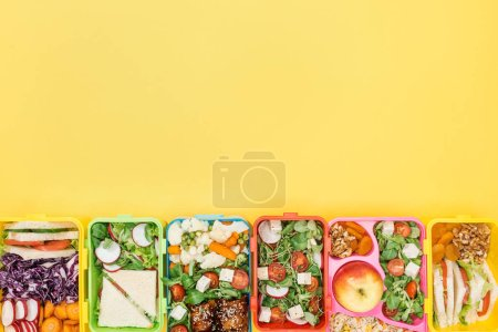 Photo for Top view of lunch boxes with food on yellow background with copy space - Royalty Free Image