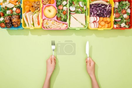 Photo for Cropped view of woman holding fork and knife near lunch boxes with food - Royalty Free Image