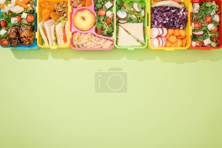 top view of lunch boxes with food on green background