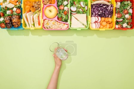 cropped view of woman holding glass of water in hand near lunch boxes with food