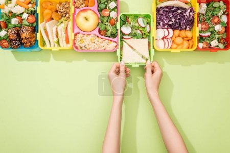Photo for Cropped view of woman choosing lunch boxes with food - Royalty Free Image