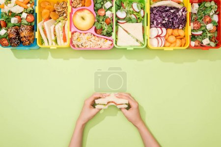Photo for Cropped view of woman holding sandwich in hands near lunch boxes with food - Royalty Free Image