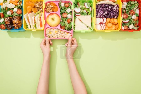 Photo for Cropped view of woman choosing lunch boxes with food on green background - Royalty Free Image