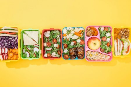 Photo for Top view of lunch boxes with delicious food on yellow background - Royalty Free Image