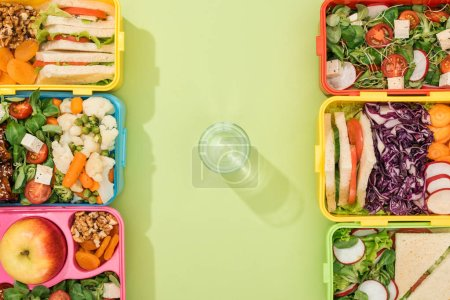 top view of lunch boxes with food near glass of water