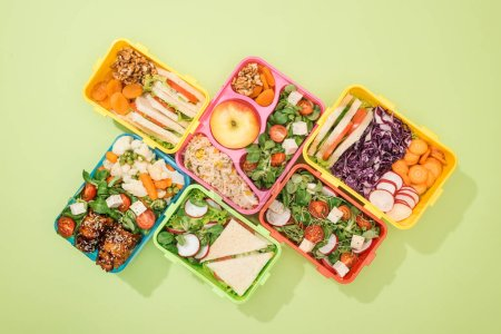 Photo for Flat lay of lunch boxes with food on green background - Royalty Free Image