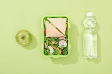 Photo for Top view of lunch box with salad and sandwiches near bottle with water and green apple - Royalty Free Image