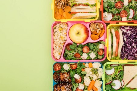 Photo for Top view of lunch boxes with food on green background - Royalty Free Image