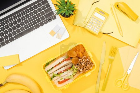 Photo pour Vue du haut de la boîte à lunch avec de la nourriture près de l'ordinateur portable et des fournitures de bureau - image libre de droit