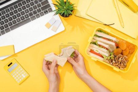Photo pour Vue recadrée de femme retenant le sandwich dans des mains près de la boîte de déjeuner, de l'ordinateur portatif et des approvisionnements de bureau - image libre de droit