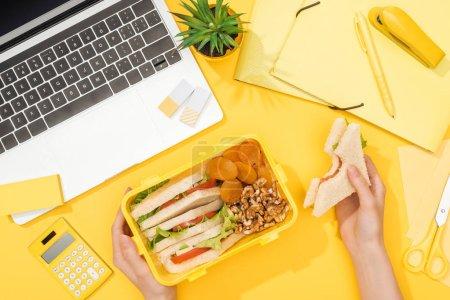 Photo pour Vue recadrée de femme retenant le sandwich dans la main près de la boîte de déjeuner, de l'ordinateur portatif et des approvisionnements de bureau - image libre de droit