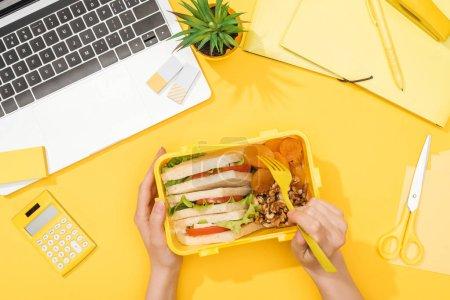 Photo pour Vue recadrée de femme retenant la boîte de déjeuner près de l'ordinateur portatif et des approvisionnements de bureau - image libre de droit
