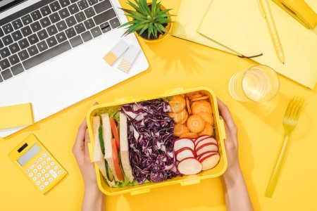 Photo for Cropped view of woman holding lunch box near laptop and office supplies - Royalty Free Image