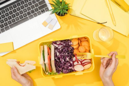Photo for Cropped view of woman holding sandwich in hand near lunch box with food, laptop, glass of water and office supplies - Royalty Free Image
