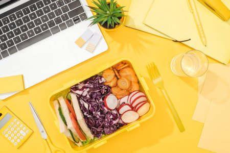 Photo for Top view of delicious lunch in box at workplace with yellow background - Royalty Free Image