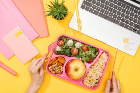 cropped view of woman holding fork over lunch box with food near laptop and office supplies