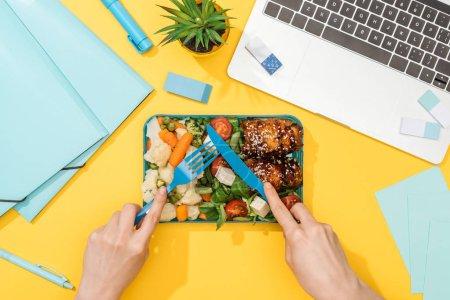 Photo pour Vue recadrée de la fourchette de fixation de femme au-dessus de la boîte de déjeuner avec la nourriture près de l'ordinateur portatif et des approvisionnements de bureau - image libre de droit