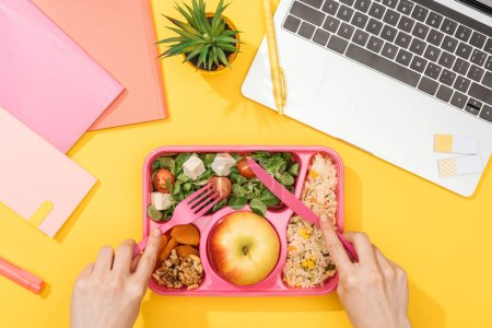 Photo for Cropped view of woman holding fork over lunch box with food near laptop and office supplies - Royalty Free Image