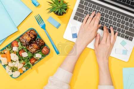 Photo for Cropped view of woman working with laptop near lunch box and office supplies - Royalty Free Image