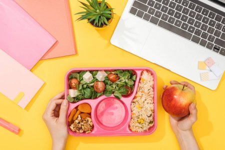 Photo for Cropped view of woman holding lunch box with food near laptop and office supplies - Royalty Free Image