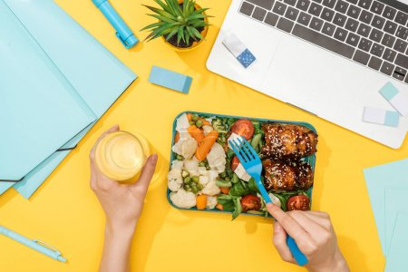 Photo for Cropped view of woman holding lunch box with food and glass of water near laptop and office supplies - Royalty Free Image