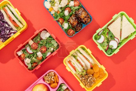 Photo for Top view of lunch boxes with food on bright red background - Royalty Free Image