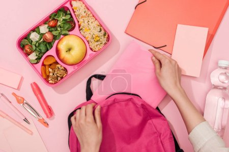 Photo for Cropped view of woman packing backpack near lunch box with food and stationery - Royalty Free Image