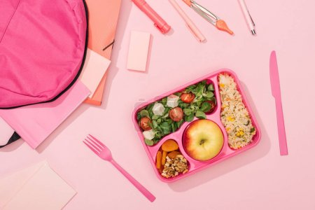 top view of lunch box with food near backpack and stationery