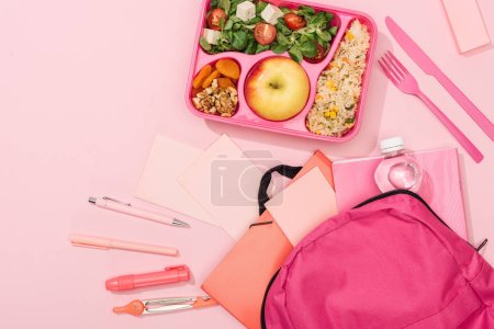 Photo for Top view of lunch box with food near backpack and stationery - Royalty Free Image