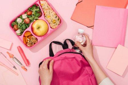 Photo pour Vue recadrée de sac à dos d'emballage de femme près de la boîte à lunch et de la papeterie - image libre de droit