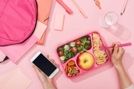 Photo pour Vue recadrée de femme avec le smartphone près de la boîte à lunch, du sac à dos et de la papeterie - image libre de droit