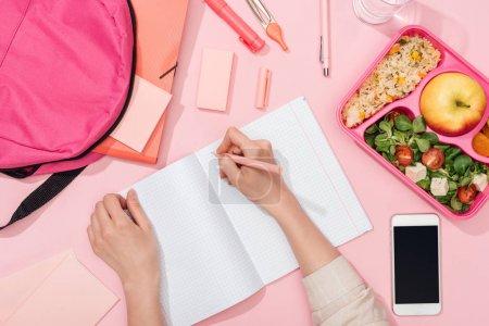 Photo pour Vue recadrée de femme écrivant dans un carnet près du sac à dos et de la papeterie - image libre de droit