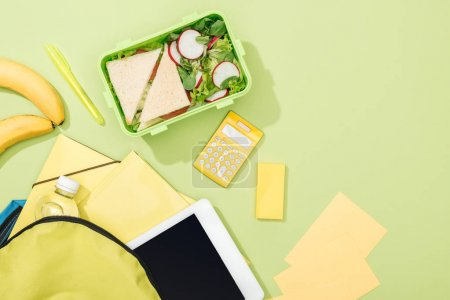 Photo for Top view of lunch box with sandwiches and salad near backpack with stationery - Royalty Free Image