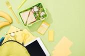 """Постер, картина, фотообои """"верхний вид на коробку с бутербродами и салатом возле рюкзака с канцелярскими принадлежностью"""""""