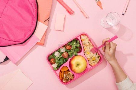 Photo pour Vue recadrée des mains de la femme avec des ustensiles en plastique sur la boîte à lunch avec de la nourriture près du sac à dos et de la papeterie - image libre de droit