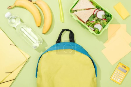 Photo for Top view of lunch box with food near backpack, bottle of water and stationery - Royalty Free Image