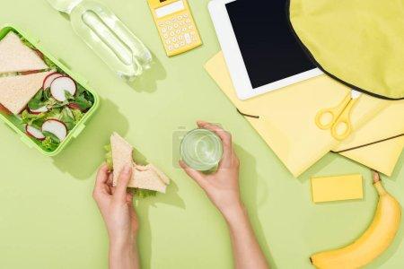 Photo pour Vue recadrée des mains de femme avec le sandwich et le verre de l'eau près de la boîte à lunch, du sac à dos, de la tablette numérique, de la bouteille d'eau et de la papeterie - image libre de droit