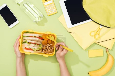 Photo for Cropped view of woman hands with plastic utensils over lunch box with food near backpack, digital tablet, bottle of water and stationery - Royalty Free Image