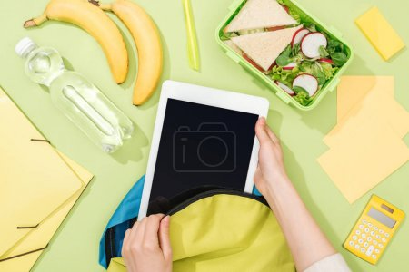 Photo for Cropped view of woman packing digital tablet in backpack near lunch box, bananas, bottle of water and stationery - Royalty Free Image