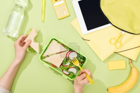 Photo for Cropped view of woman hands with sandwich, plastic utensils over lunch box with food near backpack, digital tablet, bottle of water and stationery - Royalty Free Image