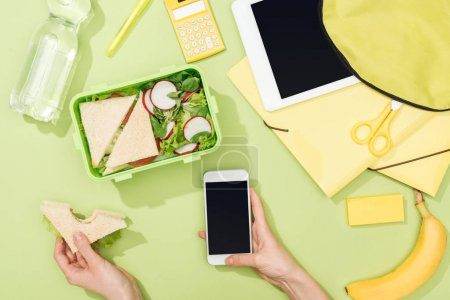 Photo for Cropped view of woman hands with sandwich and smartphone near lunch box with food, backpack, digital tablet, bottle of water and stationery - Royalty Free Image