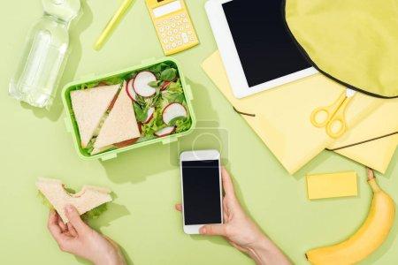 Photo pour Vue recadrée des mains de femme avec le sandwich et le smartphone près de la boîte à lunch avec la nourriture, le sac à dos, la tablette numérique, la bouteille d'eau et la papeterie - image libre de droit