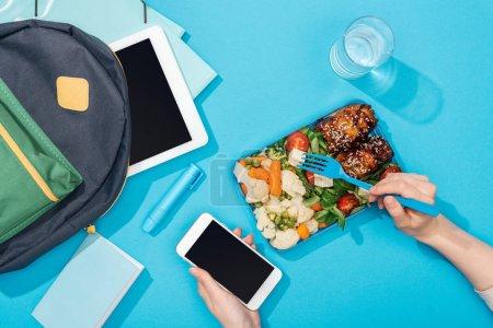 Photo pour Vue recadrée des mains de femme avec la fourchette et le smartphone près de la boîte à lunch avec la nourriture, le sac à dos, la tablette numérique, le verre d'eau et la papeterie - image libre de droit