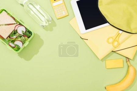 Photo pour Vue du haut du sac à dos avec la tablette numérique près de la boîte à lunch, de la papeterie et de la bouteille d'eau - image libre de droit