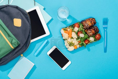 Photo for Top view of backpack with digital tablet near lunch box, smartphone, stationery, smartphone and glass of water - Royalty Free Image