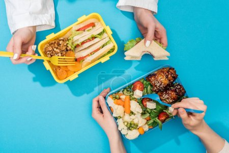 Photo for Cropped view of two women holding forks over lunch boxes with food - Royalty Free Image