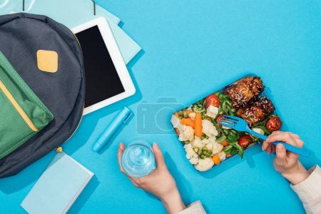 Photo for Cropped view of woman holding lunch box and glass of water near backpack with folders, stationery and digital tablet - Royalty Free Image