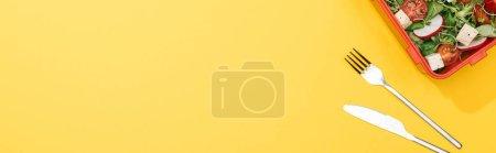 Photo pour Plan panoramique de la boîte à lunch avec fourchette et couteau sur fond jaune - image libre de droit