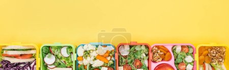 Photo for Panoramic shot of lunch boxes with tasty food on yellow background - Royalty Free Image